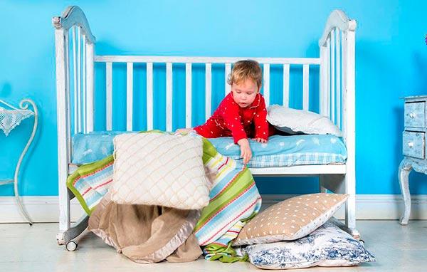 Мальчик на кровати играет подушками