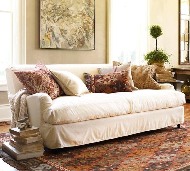 Квадратные подушки с принтом лежат на диване в красивой комнате