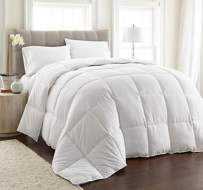 Пуховое белое одеяло лежит на кровати в красивом интерьере
