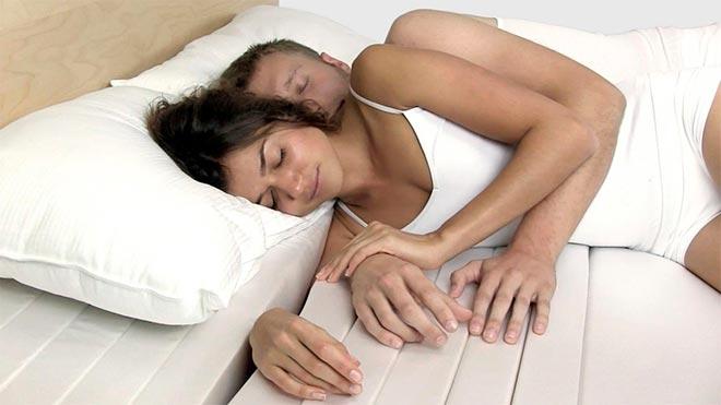 Мужчина и женщина спят в обнимку на современном матрасе
