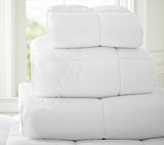 Сложенные пуховые одеяла в стопку разных размеров