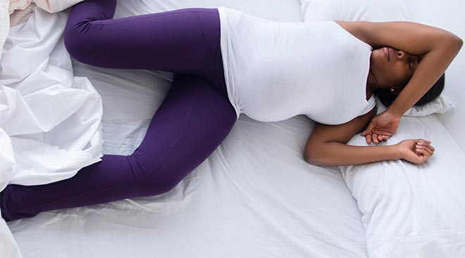 Беременная женщина лежит на кровати