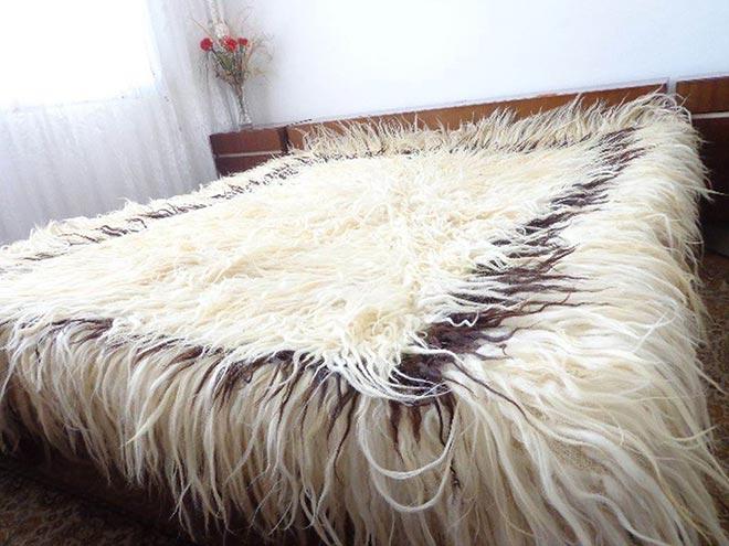 Одеяло из меха овцы на кровати