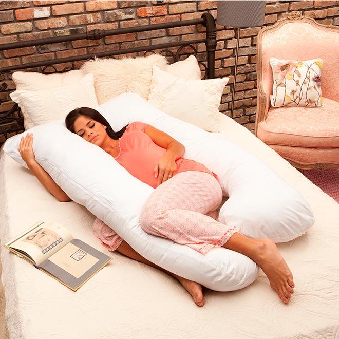 Девушка лежит на кровати с подушкой для беременных