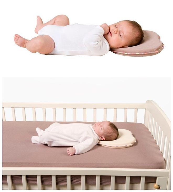 Новорожденный ребенок лежит на ортопедической подушке