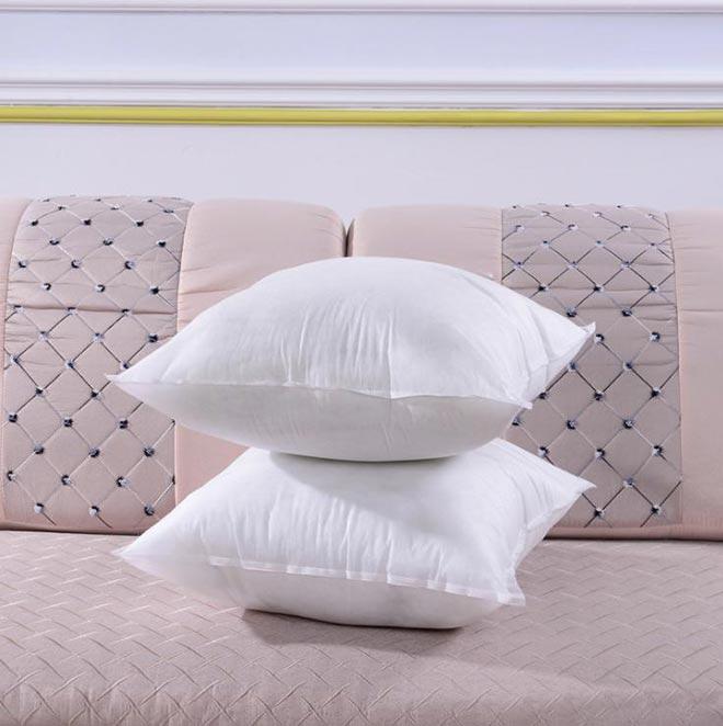 Белые подушки лежат на диване