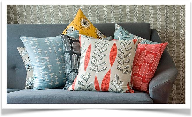 Разноцветные декоративные подушки на диване
