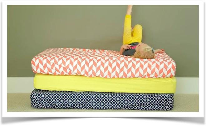 Девочка лежит на стопке разноцветных матрасов