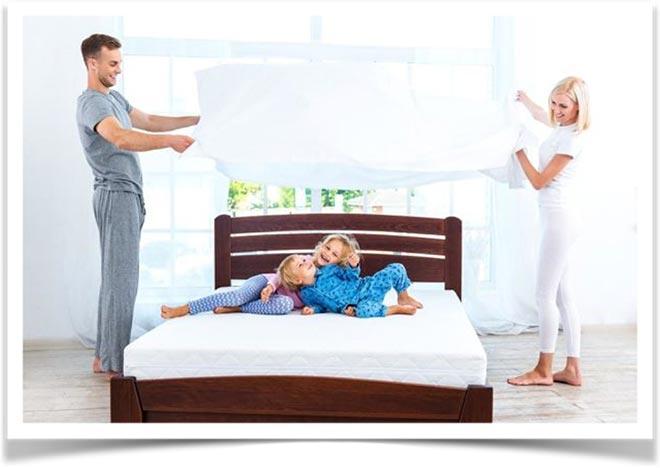 Родители ирают с детьми на кровати