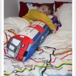 Ребенок спит в кровати с подушкой в виде поезда