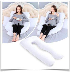 Беременная девушка пьет кофе на кровати с подушкой для беременных