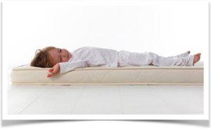Ребенок лежит на матрасе