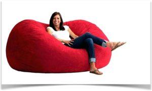 Девушка сидит в большой красной напольной подушке