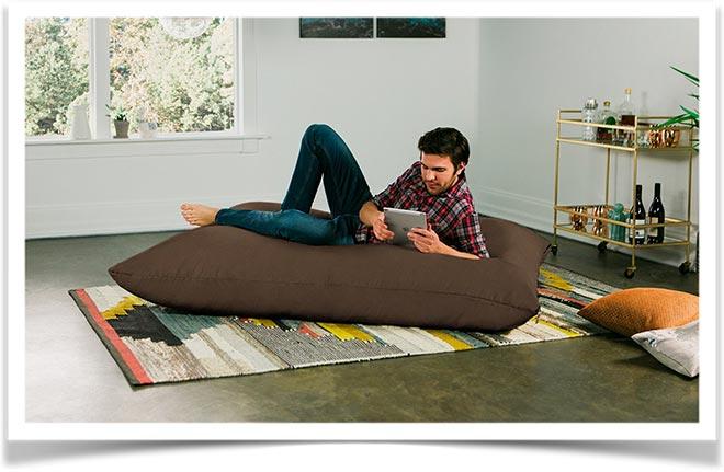 Мужчина лежит на подушке с планшетом