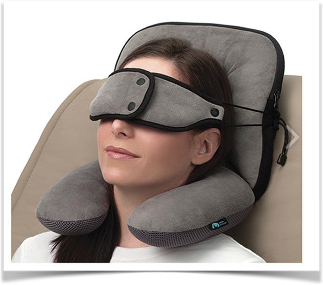 Женщина отдыхает в кресле с подушкой на шее