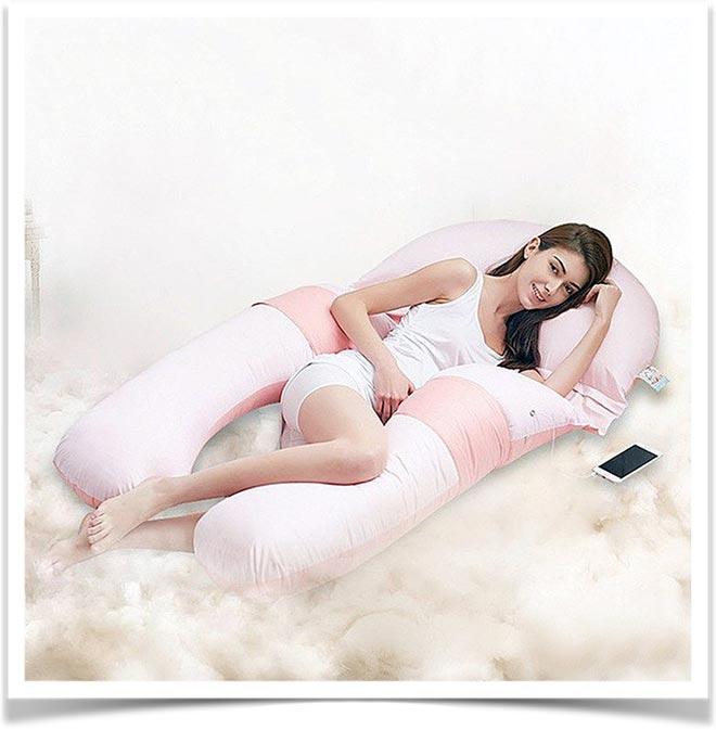 Девушка лежит на розовой подушке для беременных