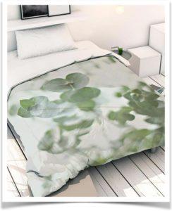 Красивое одеяло с ветками растения эвкалипт в качестве узора на кровати