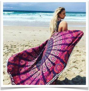 Девушка с пляжным платком идет по песку