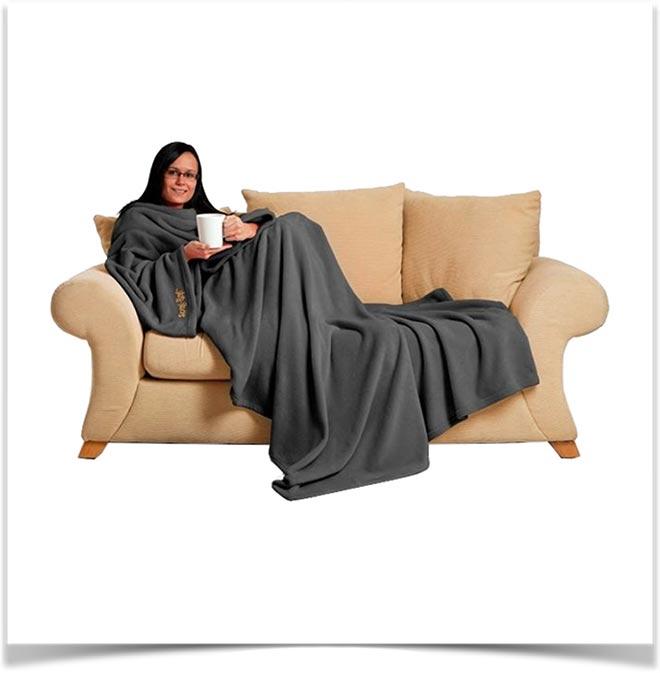 Девушка в пледе с рукавами на диване