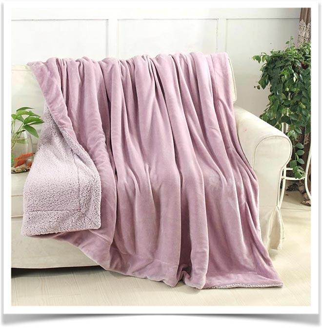 Розовый флисовый плед на бежевом диване
