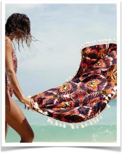 Девушка раскладывает пляжное покрывало с кисточками