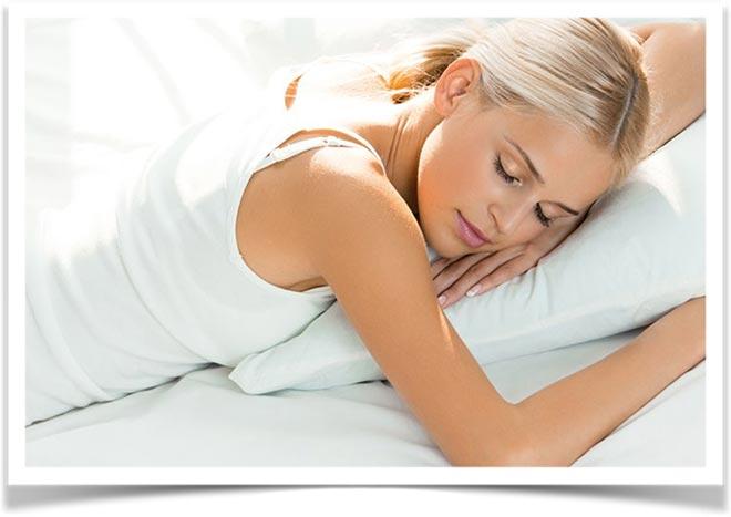Девушка со светлыми волосами спит на животе