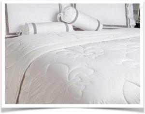 Белое стеганое одеяло с рисунком на кровати