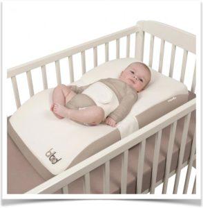 Малыш в кроватке на удобном коричневом матрасе кокон