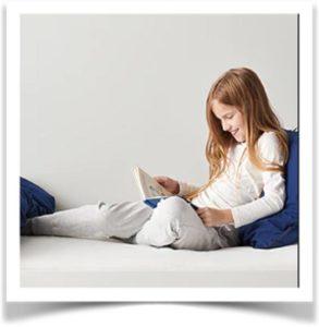 Девочка читает книгу на кровати