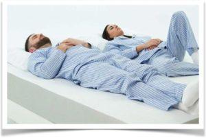 Мужчина и женщина в пижамах лежат на матрасе
