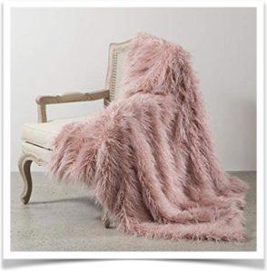Розовый плед на кресле из искусственного меха