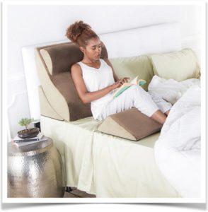 Девушка читает книгу на кровати с подушкой под спиной и ногами