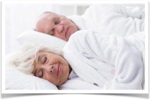 Пожилая пара спят в постели