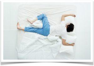 Мужчина в пижаме спит на животе