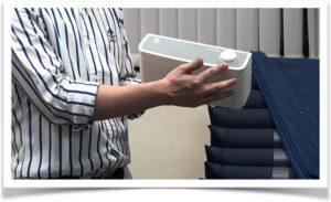 Мужчина держит компрессор от противопролежневого матраса