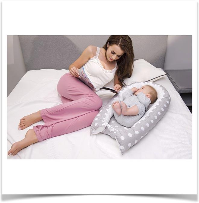 Мама и ребенок на коконе лежат рядом в кровати