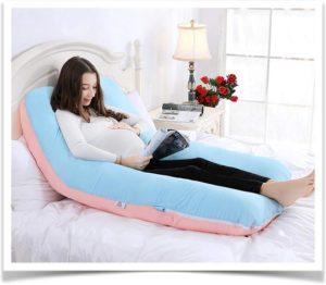 Беременная девушка сидя читает журнал облокотившись на подушку
