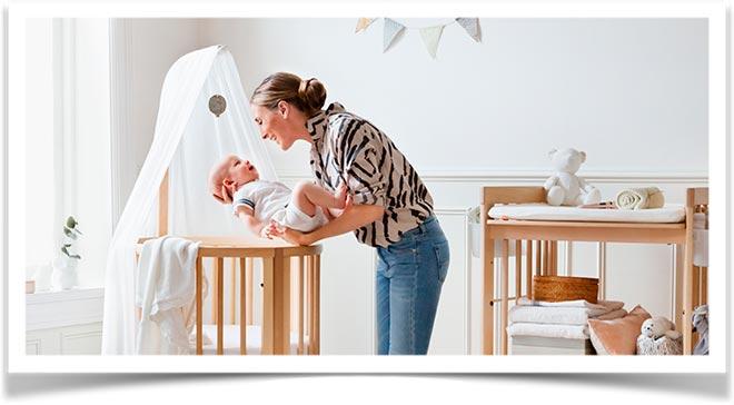 Мама кладет своего ребенка в круглую кроватку