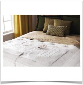 Маленький матрас с подогревом для ног лежит на кровати