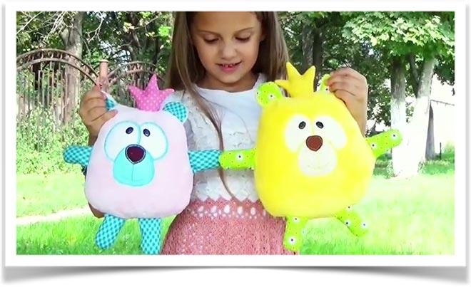 Девочка показывает своих игрушк-мишек