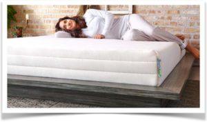 Девушка в белом лежит на большой кровати