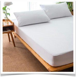 Кровать с матрасом и подушками в комнате