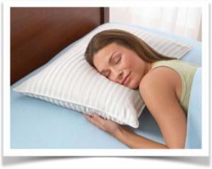 Молодая женщина спит на полосатой подушке