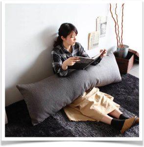Девушка сидит с подушкой бревном и читает книгу