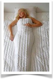 Женщина спит под белым утяжеленным одеялом