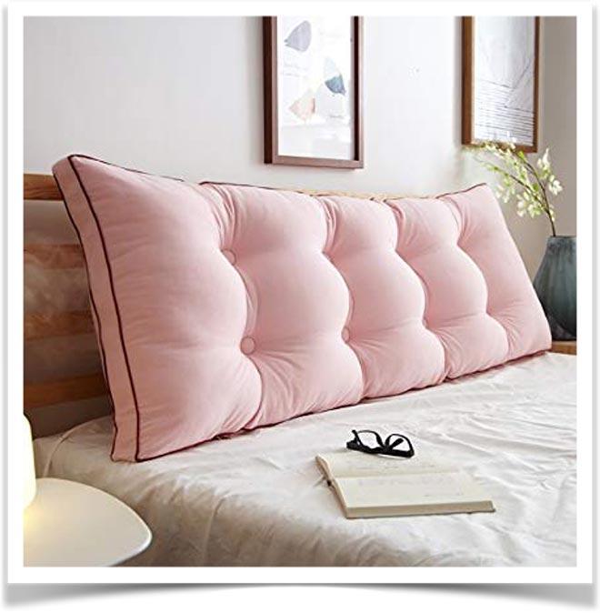 Розовая подушка спинка на большой кровати
