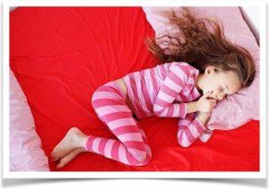 Девочка в полосатой пижаме спит на красной кровати