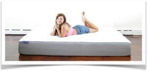 Женщина в шортах лежит на матрасе