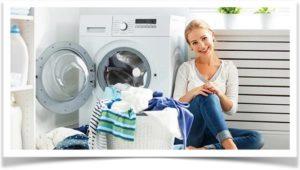 Девушка с бельем сидит возле стиральной машинки