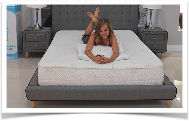 Девушка с мобильным телефоном лежит на кровати